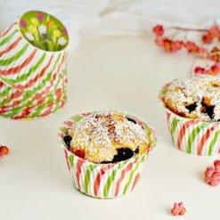 Muffin con yogurt e mirtilli in pirottini con fantasia a fiori verdi e rossi